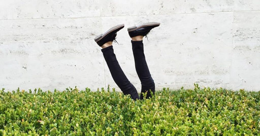 Concept image of a lawyer upside-down with their feet sticking out of the bushes upon making law practice mistakes