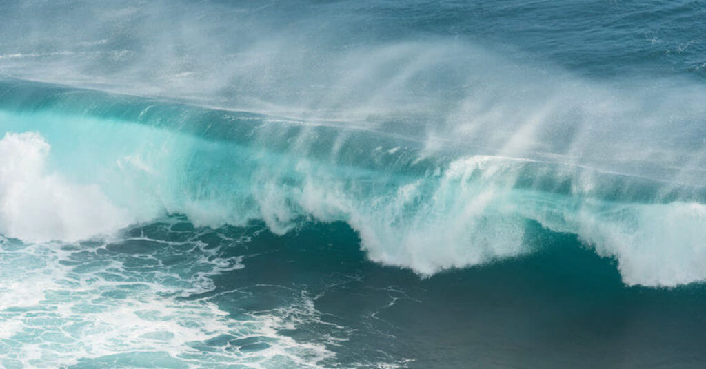 close up of turquoise and blue wave crashing on the shore of the beach