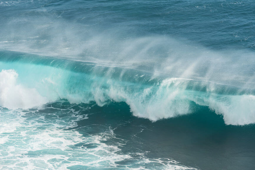 A big blue and turquoise ocean wave crashing