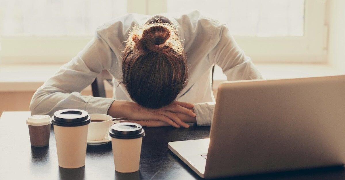 Stressed lawyer with her head down at her desk