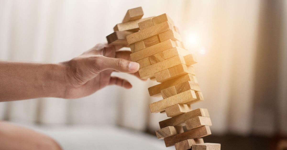 A falling Jenga tower on an office desk, suggeting the concept of failure for law practices.