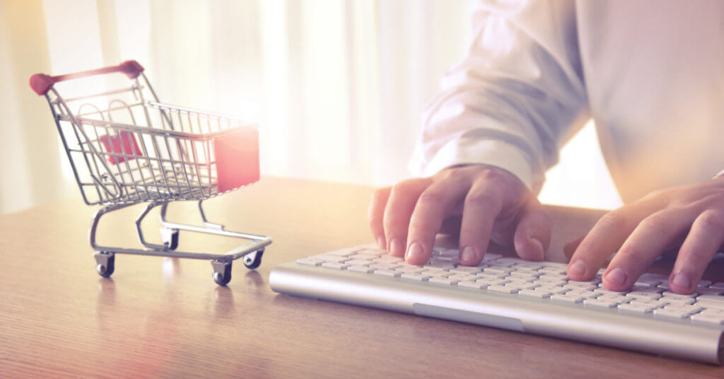 Tiny shopping cart next to hands on the keyboard on a lawyer's desk.