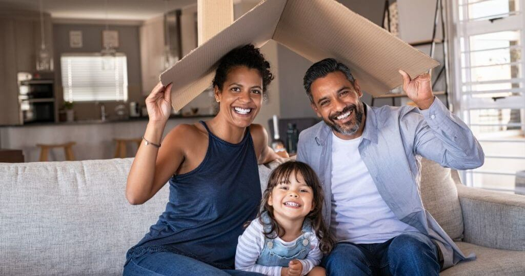 Happy parents and child playing in living room that may be new clients for a lawyer starting an estate planning practice.
