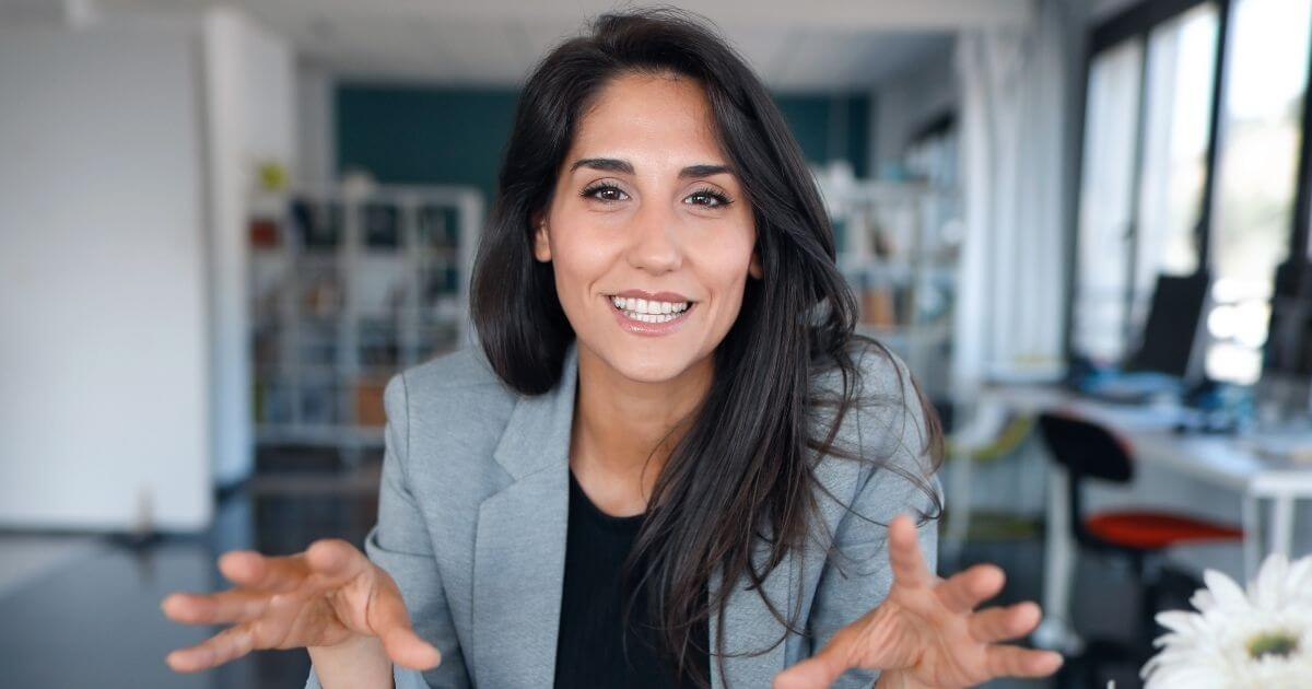 Dark haired woman in grey blazer sits at desk offering tips for building a virtual law firm.