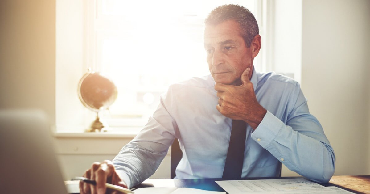 Businessman sits at his desk, sunlight streaming into room through window behind him, while he contemplates how to make money as a solo lawyer.