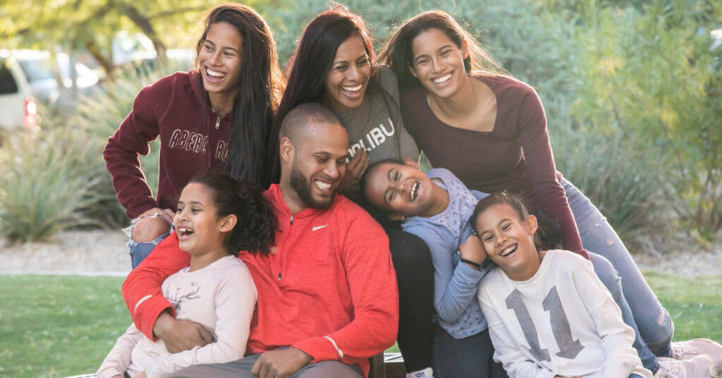 Shane Young, estate planning lawyer, with her husband and 5 daughters, laughing and enjoying outdoor time together.