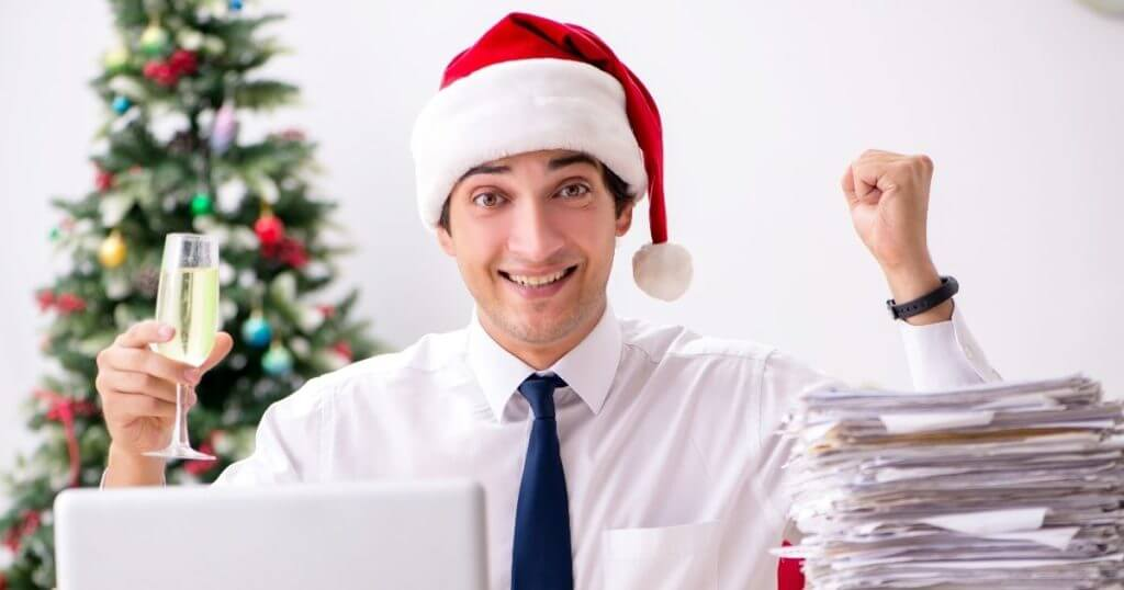 Lawyer sits at desk with piles of paper and a Christmas tree in the background.