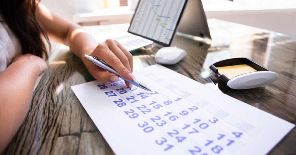 Lawyer sits at her desk examining calendar and spreadsheets