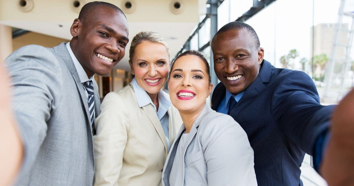 Small law office team taking group pic after having learned how to manage a small law firm.