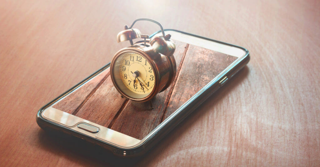 A small, brown, antique alarm clock sits atop a cell phone on a desk