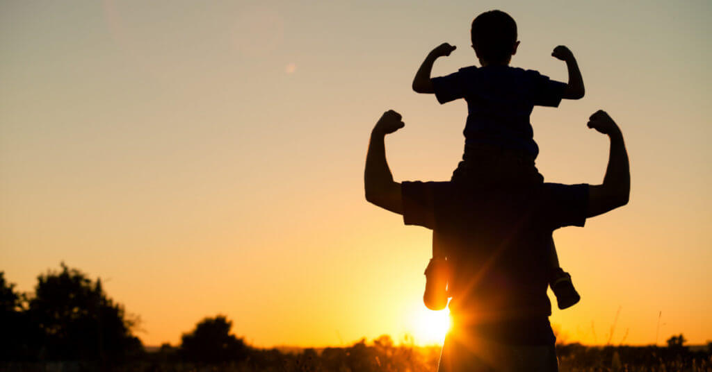 silhuette of father and son, making 'strong arms' in front of the bright sunset