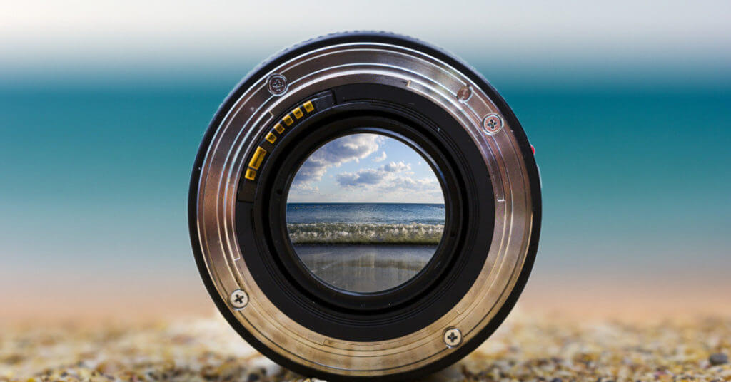 Close up of camera lens with beach and ocean in focus against blurred beach scene background, used as metaphor for focusing your law practice area.