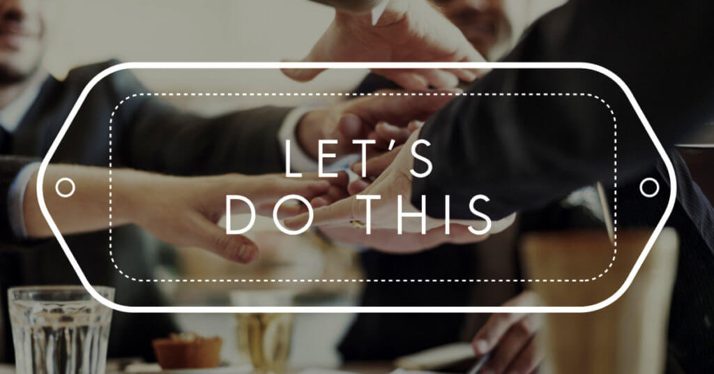 "Graphic overlay of the words ""Let's Do This"" over an image of several business peoples' hands coming together at a table in solidarity"