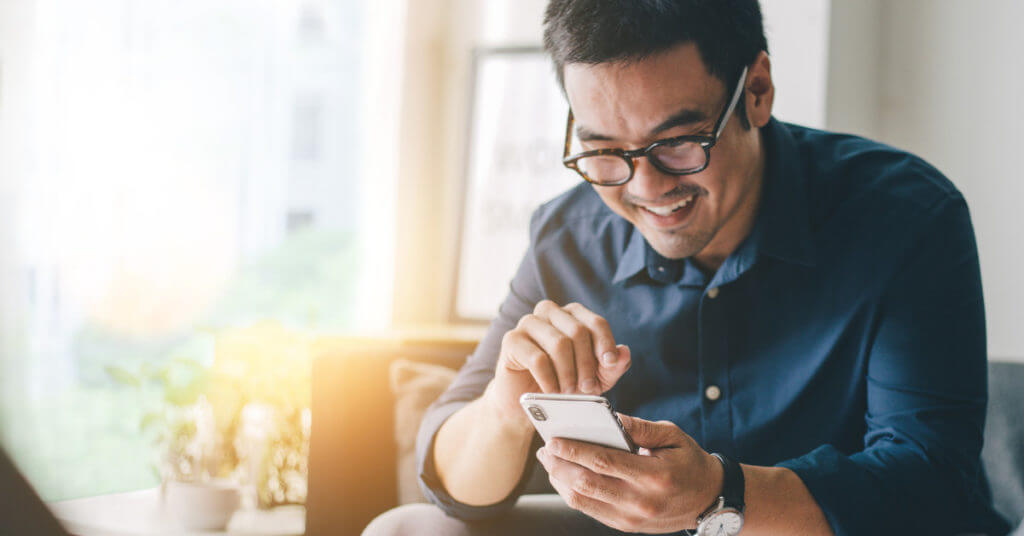 Asian man smiling while using his cell phone in a sunlit room.