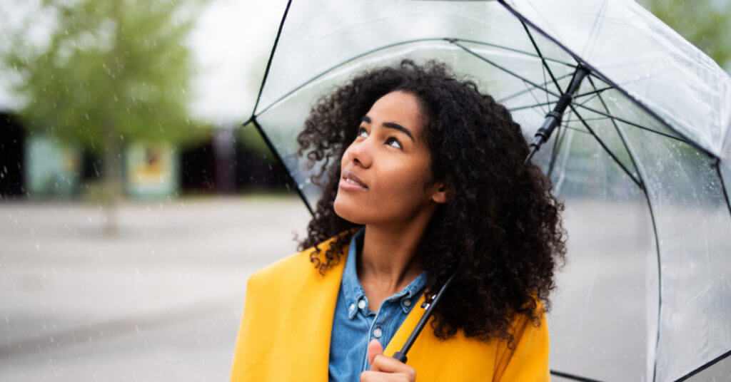 woman in yellow coat stands under a clear umbrella looking up at a rainy sky.