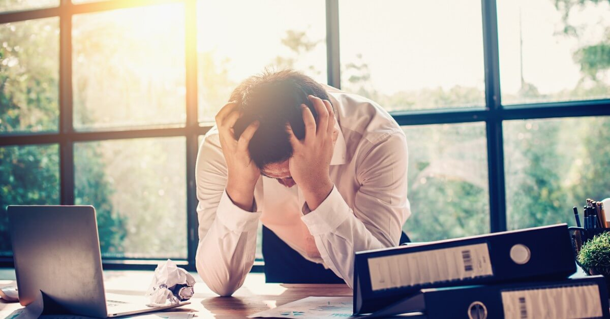 Lawyer at his desk holding his head in his hands due to burnout,