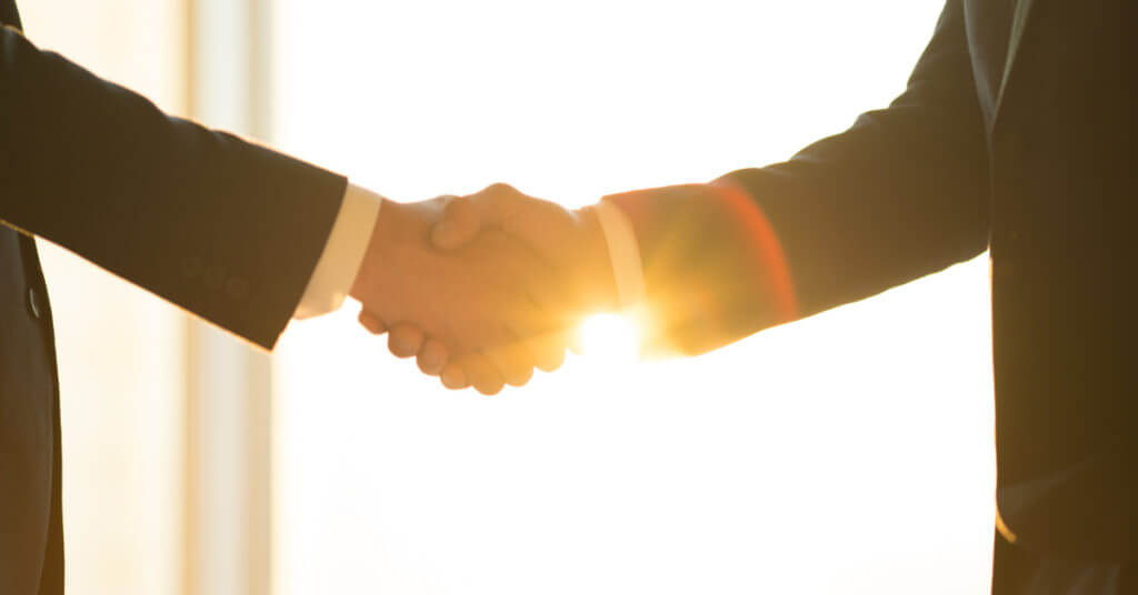 Lawyer shakes hand with new client against a sunny background