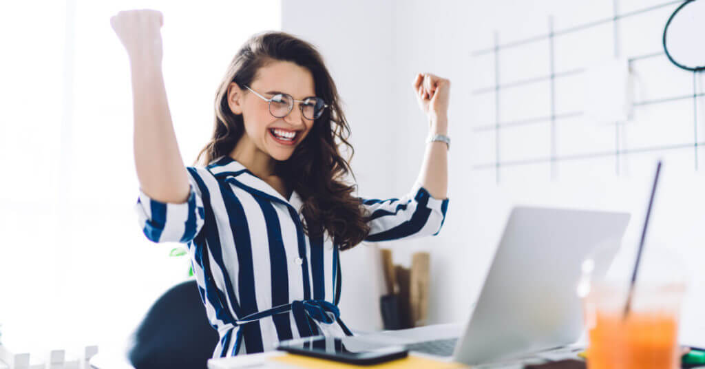 Successful estate planning lawyer sits at desk with fists in the air celebrating success.