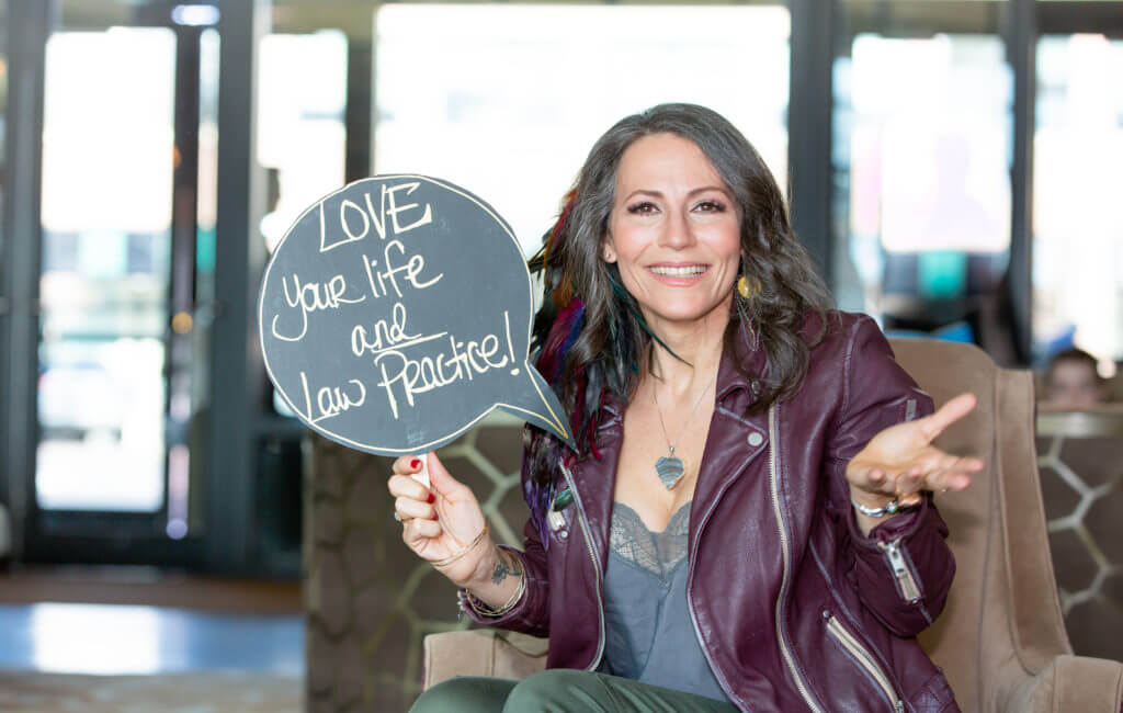 """Ali Katz, New Law Business Model Founder and CEO, holding sign that says """"Love Your Life and Law Practice"""""""
