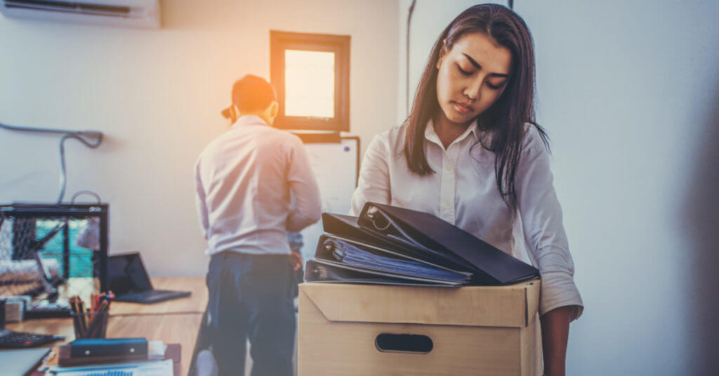 Woman carrying a box and files out of her office after experiencing Biglaw burnout and quitting her law job.