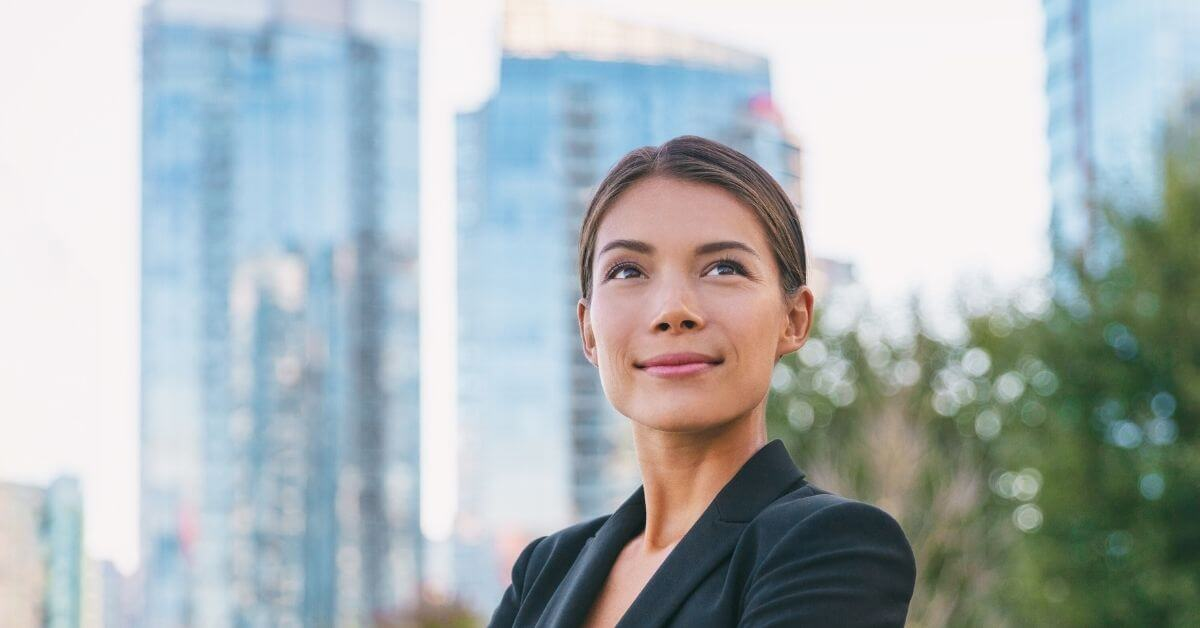 Woman in suit standing in front of city skyline, thinking about how lawyers impact positive change.