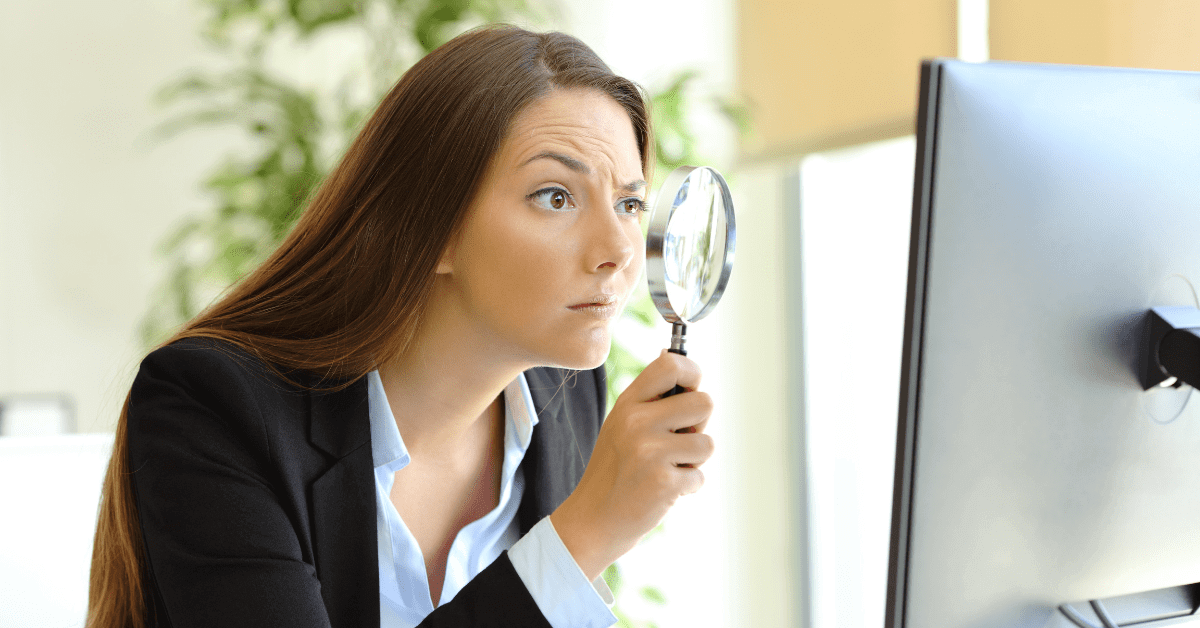 Female lawyer in suit sits at desk holding up magnifying glass to computer screen as if she is searching for a life as a lawyer that works.