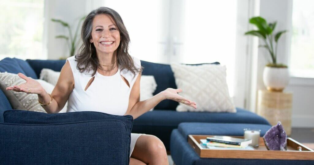 Ali Katz, New Law Business Model founder sits on couch with her hands up in the air.