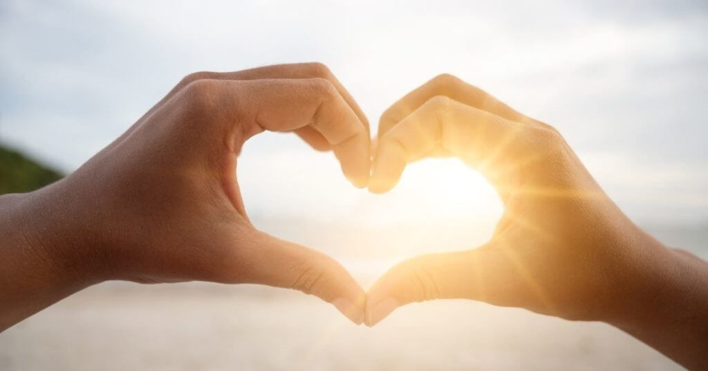 Two hands making a heart in front of shining sun, in honor of Love Your Lawyer day.
