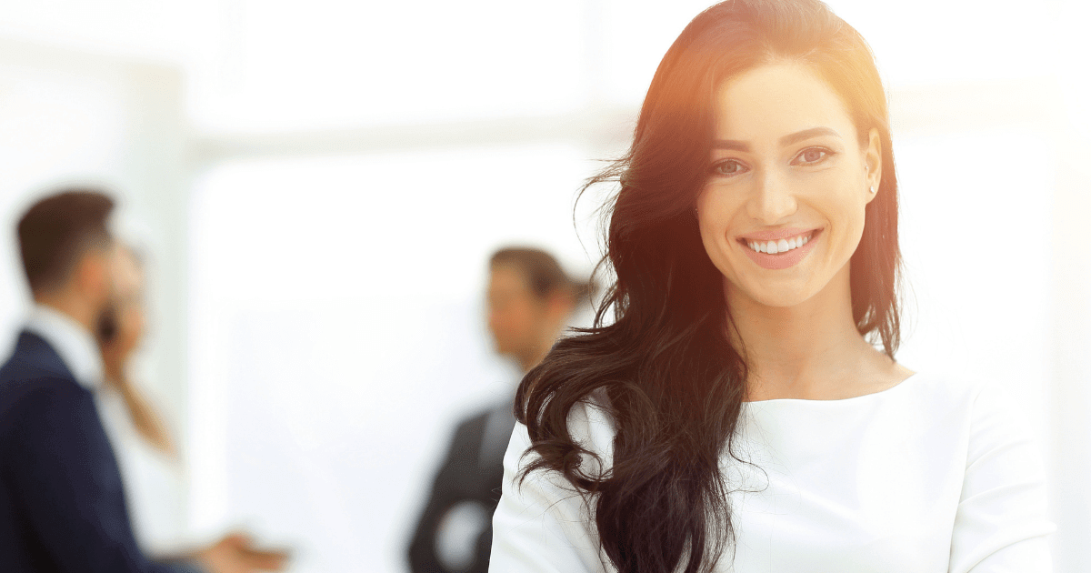 Female law practice owner stands in foreground of office scene, looking forward and smiling.