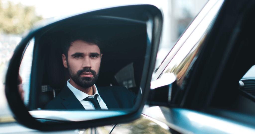 Reflection of driver's side mirror shows man in suit staring back.