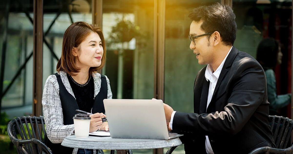 Female lawyer sits at cafe table with male lawyer in suit, discussing success in law practice.