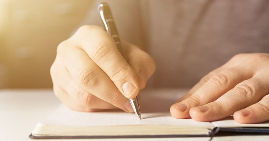 Man's hands writing in a journal, illustrating the power of journaling to transform your law practice.
