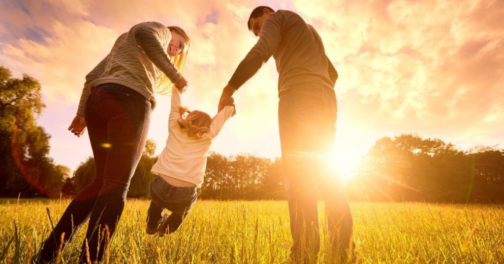 Young family playing in meadow at sunset.