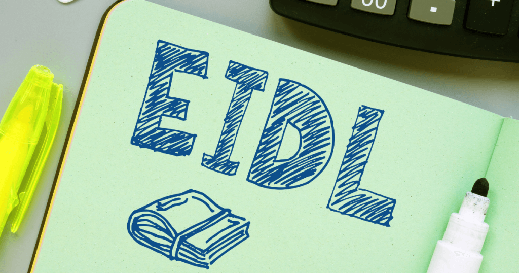 The letters EIDL, which stands for Economic Injury Disaster Loan, drawn in a journal on a lawyer's desk.